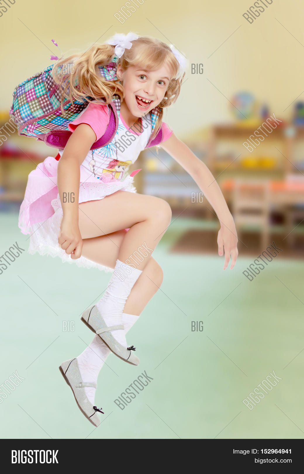 b3b85e26fa20 Cheerful little girl in a pink short skirt hurries to school.In ..