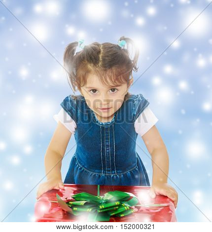 Caucasian little girl in a blue dress with short sleeves , kneeling around a red box with a bow. Close-up.Blue Christmas festive background with white snowflakes.
