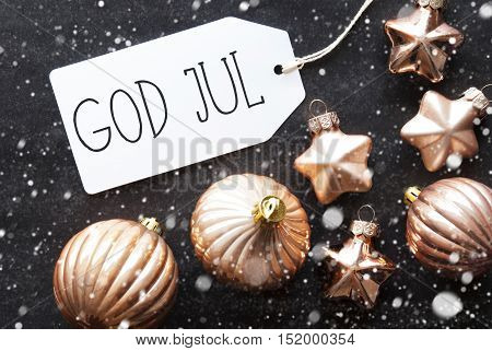 Label With Swedish Text God Jul Means Merry Christmas. Bronze Christmas Tree Balls On Black Paper Background With Snowflakes. Christmas Decoration Or Texture. Flat Lay View