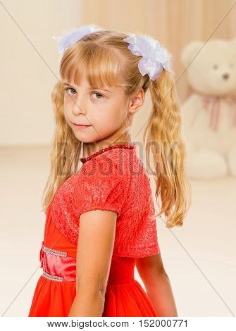 A very beautiful little girl with long, blonde ponytails on her head in a bright orange dress.On the background of the nursery , in the background a Teddy bear.