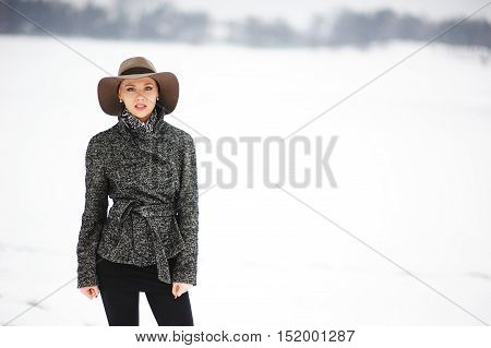 Portrait of elegant young girl in jacket and hat on the street in winter Park