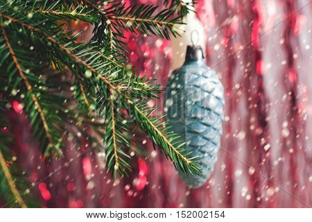 Christmas toy - a bump on a spruce branch on blurred background with falling snow