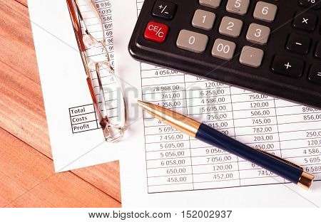 Calculator pen and glasses lying on the financial statements. Business concept