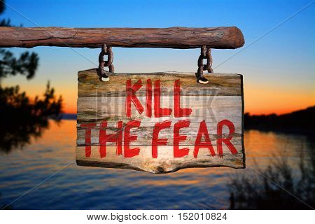 Kill the fear motivational phrase sign on old wood with blurred background