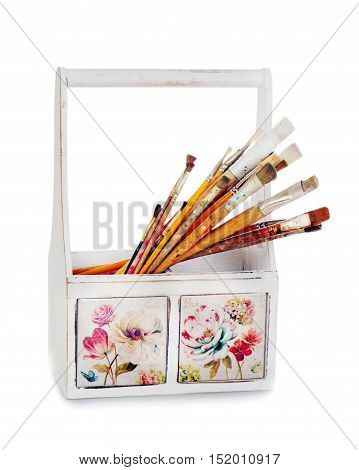 Old wooden box with paint brushes isolated on white background.