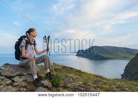 Young woman with backpack look at lake from high point of view.