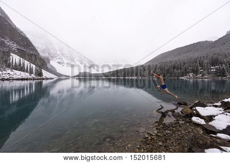 Man jumps into freezing cold Moraine lake after a snowfall