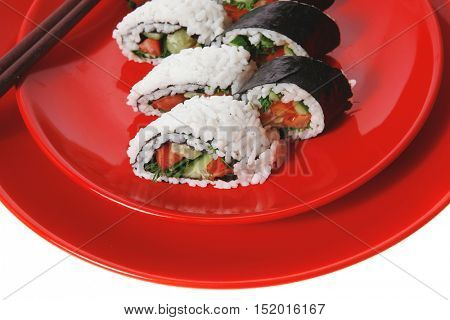 fresh japan maki and onigiri sushi on red plate with sticks isolated on white background