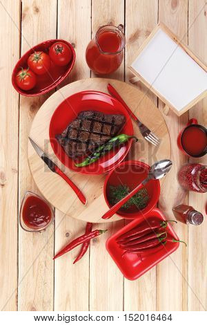 red theme lunch : fresh grilled bbq roast beef steak red plate green chili  soup  sauce paprika   glass ground pepper american   modern cutlery served  wooden plate  table empty nameplate menu board