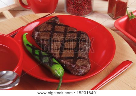 red theme lunch fresh grilled bbq roast beef steakred plate green chili tomato soup ketchup sauce  glass ground pepper american peppercorn  modern cutlery  wooden plate  table empty nameplate menu