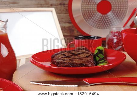red theme lunch fresh grilled bbq roast beef steak on red plate green chili tomato soup ketchup sauce paprika glass ground pepper american modern cutlery  wooden plate  table empty nameplate menu