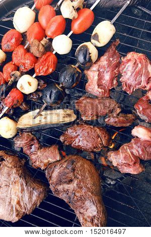 fresh raw beef fillet steak red meat with tomatoes and eggplant on skewers on big round barbecue brazier grid full with ready charcoal