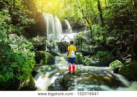 man stand in front of beautiful Waterfall in deep forest fresh green rain season