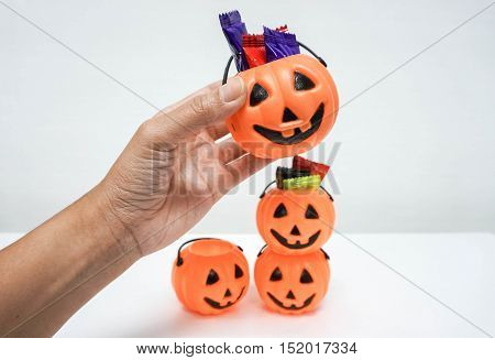 woman hold orange pumpkin with colorful candies for Halloween party