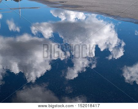 Reflection of white clouds in a puddle in a city street urban scene