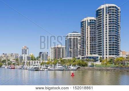 Modern waterfront apartments and yachts in marina in Brisbane during daytime