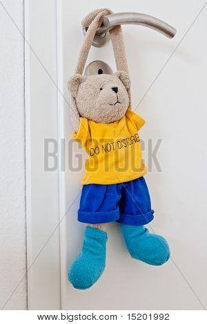 Teddy hanging at door handle