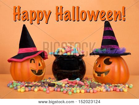 Halloween candy worms spilling from a black cauldron with hard candies and chocolate candy on orange table orange background. Small pumpkin witch jack o lanterns on each side. Happy Halloween text