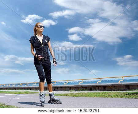 Young, beautiful and fit girl over sky background. Sporty woman on skates.