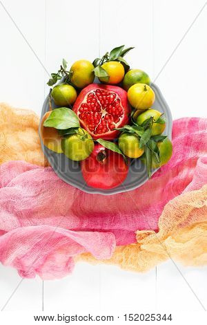 Beautiful set of fruits pomegranate, tangerine, pear on pink textile and white wooden background. Fashion food