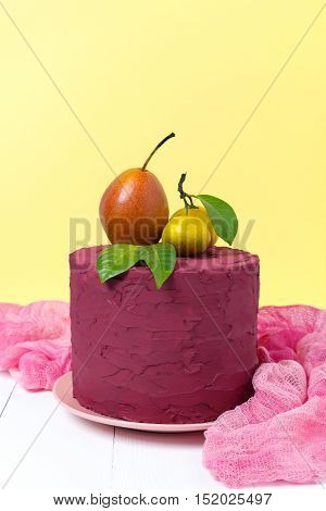 Stylish colors Marsala cake decorated with pears and tangerines on a pastel yellow background. Fruit still life