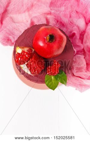 Top view of homemade cake decorated with pomegranate seeds and pink textile on a white wooden background