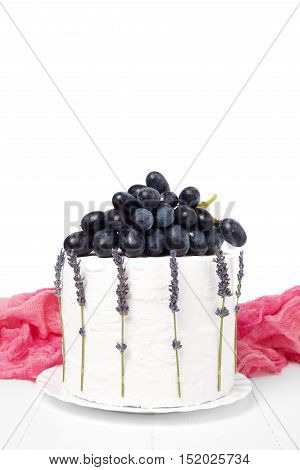 Homemade sour cream cake decorated with grapes and lavender on a white wooden background. Fruit still life