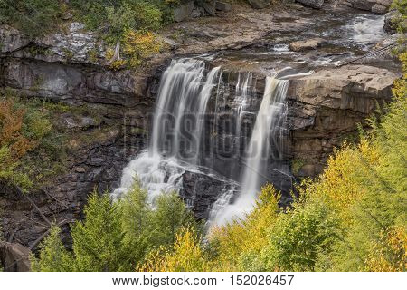 Blackwater Falls near Davis West Virginia pours over a sandstone cliff surrounded by colorful fall foliage.