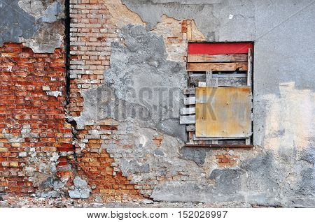 Gray wall of abandoned building with peeling plaster red brick and the boarded-up window.