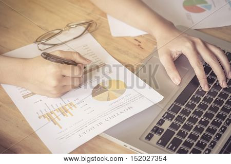 close up Business girl using laptop with holding pen point stock market chart and on wood desk. vintage effect.
