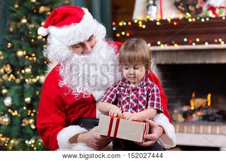 Father weared Santa Claus and kid boy open gift box sitting near by Christmas tree at fireplace