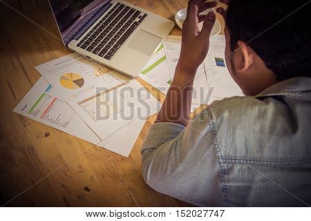 stressed business man with graph document statistic and laptop on wood desk vintage filter