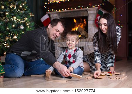 Happy parents with their son play with model railway near christmas tree in room