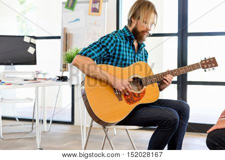 Man playing guitar in office