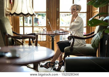 Attractive blonde girl in glasses sits on armchair at the table in the restaurant and talks on the cell phone. Her right hand is on the laptop. Woman wears black dress and sandals, a white cloak.