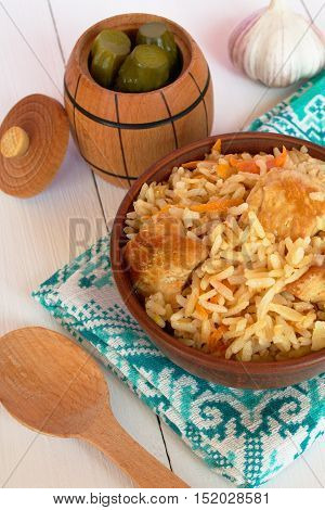 Pilaf with meat from a bowl on a wooden Board and white background, barrel pickles, garlic, wooden spoon