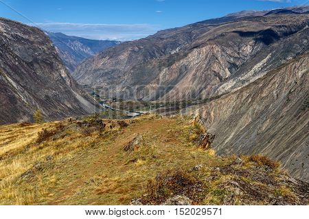 The picturesque autumnal top view on the mountains cliffs and beautiful winding river in a valley between the mountains on the background of blue sky and clouds