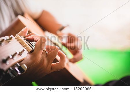 close up Man hand playing acoustic guitar. vintage effect. release or relax concept.
