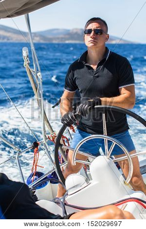 Young man skipper steers wheel sailing yacht boat. Vacation, holidays, travel.