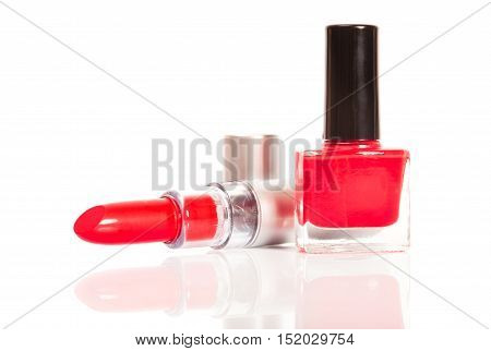 Red lipstick and nail polish on a white background