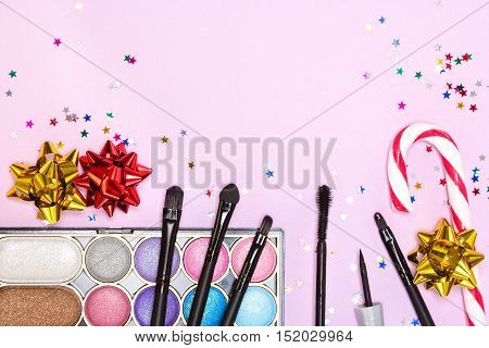 Makeup for party. Bright color glitter eyeshadow, mascara, eyeliner, red lip gloss, make up brushes and applicator with candy cane, gift wrap bows and confetti on pink background. Copy space