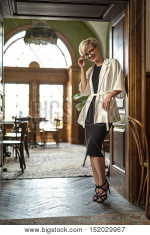 Smiling blonde girl in glasses stands in the doorway in the hall of the restaurant. She looks into the camera and holds glasses with right hand. Woman wears a black dress and sandals, a white coat.