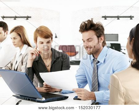 Young businesspeople sitting at desk in busy office, working.