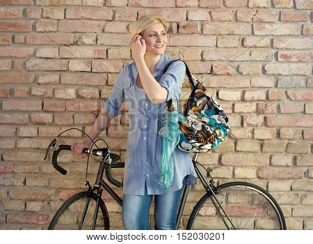 Young blonde woman with bicycle.