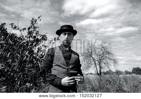 Young bearded priest on tree background. Black and white photography
