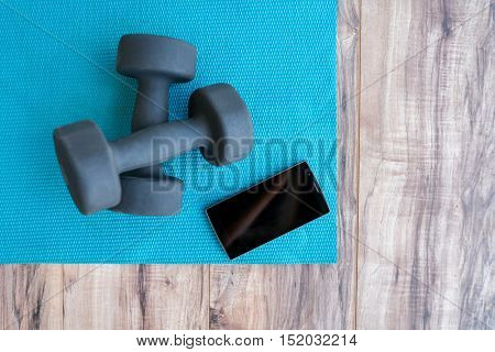 Fitness at home: free weights, yoga mat, mobile phone app. Dumbbells on blue exercise mat and smartphone for gym or health progress app. Smartphone showing copy on screen for exercising videos online.