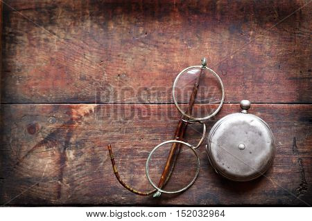 Old spectacles near closed pocket watch on wooden background