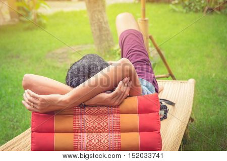 Rear view of man relaxing on chair at home with thailand style