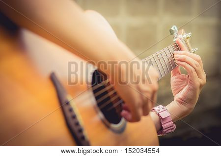 close up Woman playing acoustic guitar. vintage effect. selective focus. release concept.