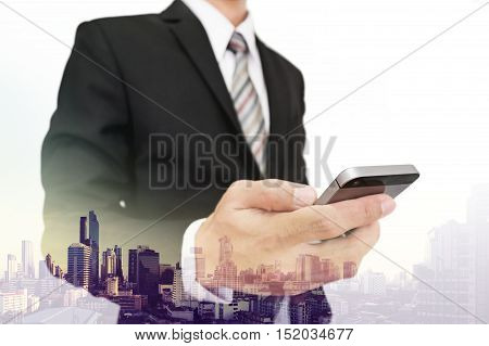 Double exposure businessman using smartphone with city view background